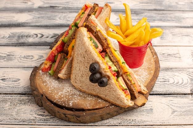 Vista frontal de sanduíches saborosos de torradas com presunto de queijo por dentro e batatas fritas na madeira