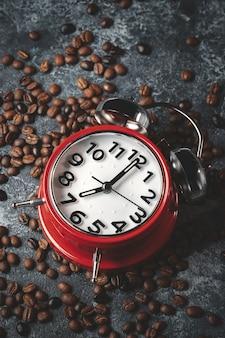 Vista frontal de sementes de café marrom com superfície escura de relógios vermelhos