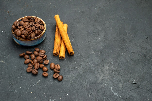 Vista frontal de sementes de grãos de café em uma tigela em paus de canela em um fundo escuro isolado.