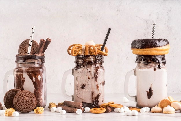 Vista frontal de sobremesas em potes com biscoitos e rosquinhas
