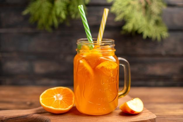Vista frontal de suco de frutas frescas em um copo servido com tubos, maçã e laranja em uma tábua de madeira sobre uma mesa marrom
