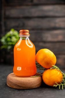 Vista frontal de suco de laranja em garrafa na placa de madeira laranjas na superfície isolada marrom