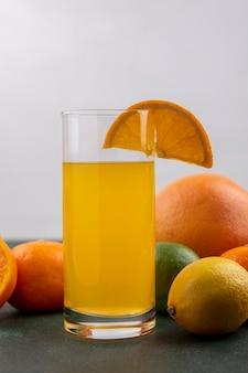 Vista frontal de suco de laranja em um copo com limão, limão, laranjas e toranja