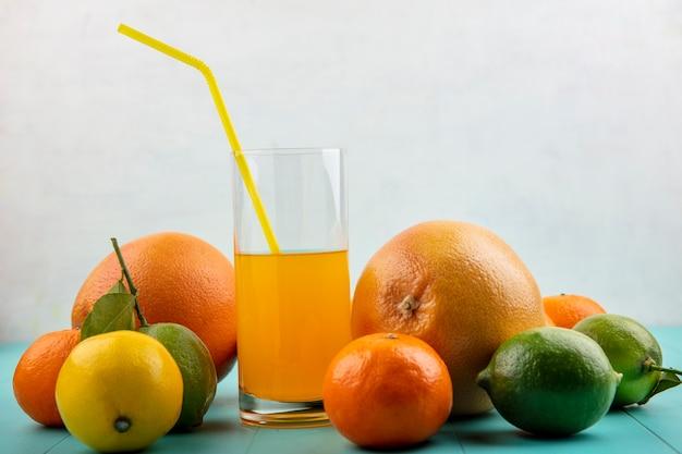 Vista frontal de suco de laranja em um copo e canudo amarelo com laranja, toranja e limão com limão