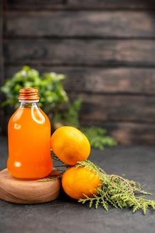 Vista frontal de suco de laranja em uma tábua de servir de madeira em vasos de plantas de laranjas frescas em uma superfície isolada marrom