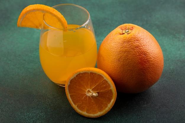 Vista frontal de suco de laranja em vidro com laranja e toranja em fundo verde