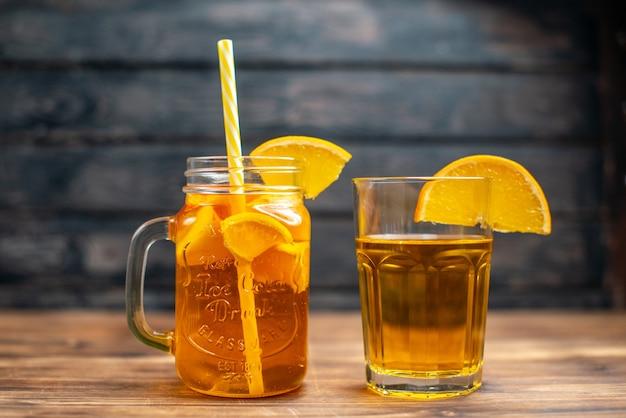 Vista frontal de suco de laranja fresco dentro da lata com canudo escuro.