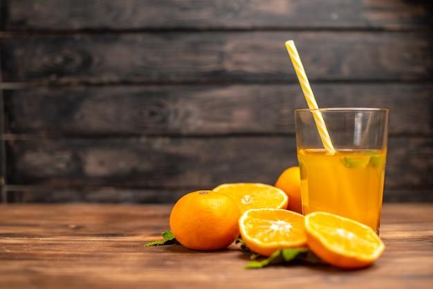 Vista frontal de suco de laranja fresco em um copo servido com tubo de hortelã e laranjas inteiras cortadas no lado esquerdo em uma mesa de madeira