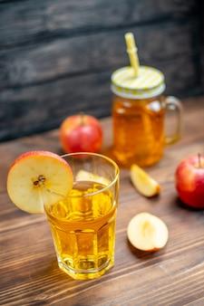Vista frontal de suco de maçã fresco com maçãs frescas no piso de madeira marrom foto coquetel de frutas cor