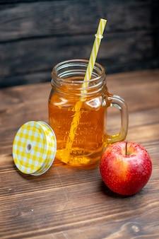 Vista frontal de suco de maçã fresco dentro da lata com maçã fresca no bar escuro.