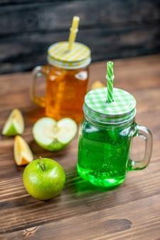 Vista frontal de suco de maçã fresco dentro de latas em cores de barra de coquetéis de frutas escuras