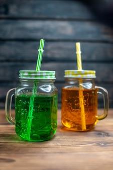 Vista frontal de suco de maçã fresco dentro de latas na cor escura da foto da bebida de frutas