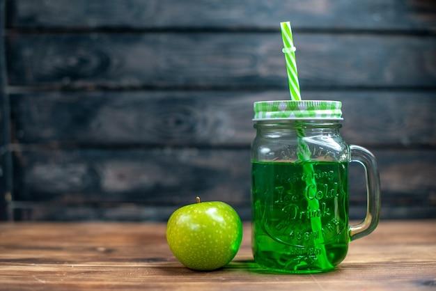 Vista frontal de suco de maçã verde dentro da lata com maçã verde fresca na mesa de madeira.