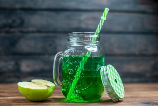 Vista frontal de suco de maçã verde dentro da lata com maçãs frescas na mesa escura.