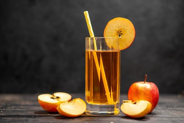 Vista frontal de suco fresco natural delicioso em dois copos com limão de maçã vermelha em fundo preto