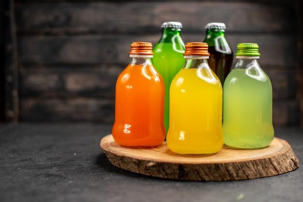 Vista frontal de sucos de cores diferentes em garrafas na placa de madeira na superfície de madeira escura