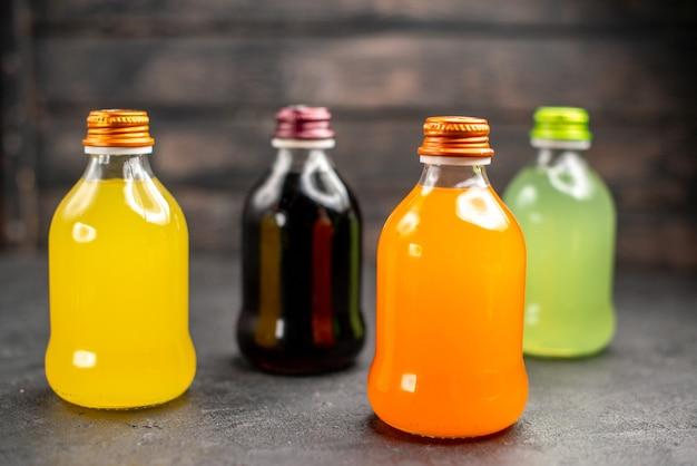 Vista frontal de sucos de frutas coloridos em garrafas