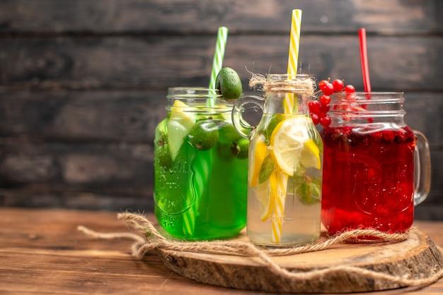 Vista frontal de sucos naturais de frutas orgânicas em garrafas servidas com tubos em uma tábua de madeira