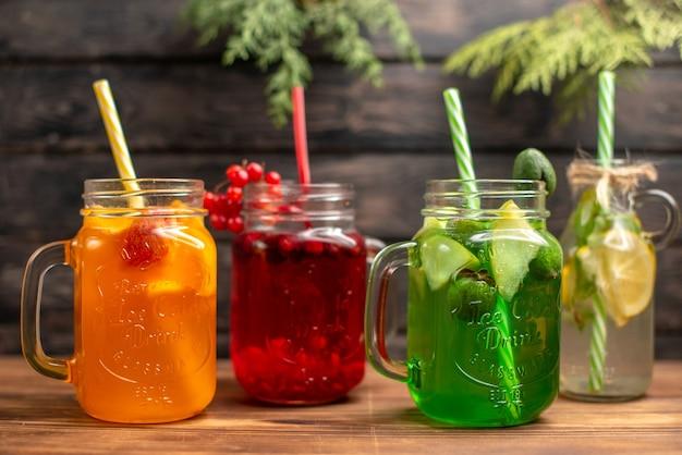 Vista frontal de sucos naturais orgânicos em garrafas servidas com tubos e frutas em um fundo de madeira marrom