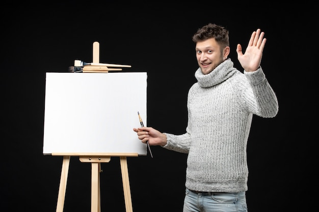 Vista frontal de talentoso pintor masculino com expressão facial emocional mostrando cinco em preto