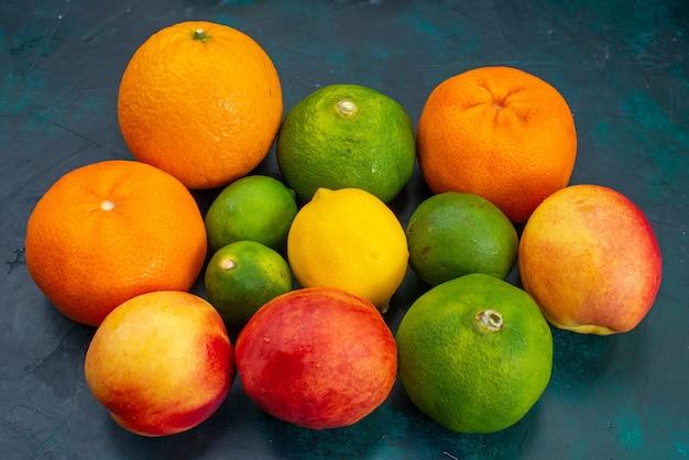 Vista frontal de tangerinas e pêssegos frutas frescas e suaves em azul-escuro vitamina de frutas cítricas exóticas