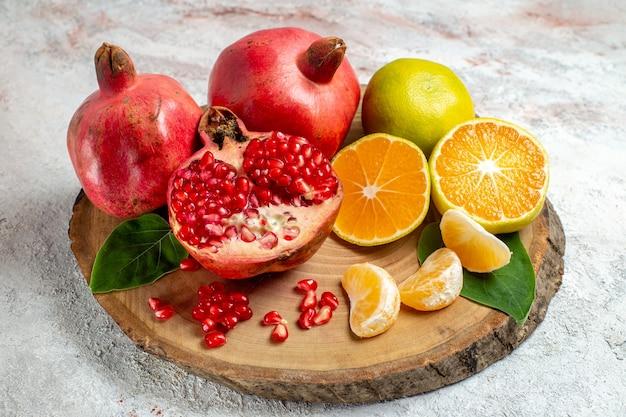 Vista frontal de tangerinas e romãs frutas frescas e maduras no espaço em branco