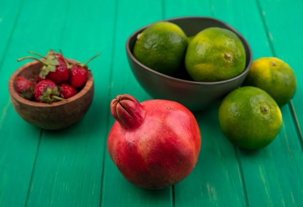 Vista frontal de tangerinas em uma tigela e romã com morangos em uma parede verde
