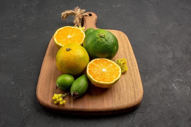 Vista frontal de tangerinas frescas com feijoa no espaço escuro