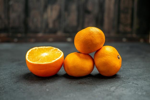 Vista frontal de tangerinas frescas cortadas em laranja em espaço livre escuro