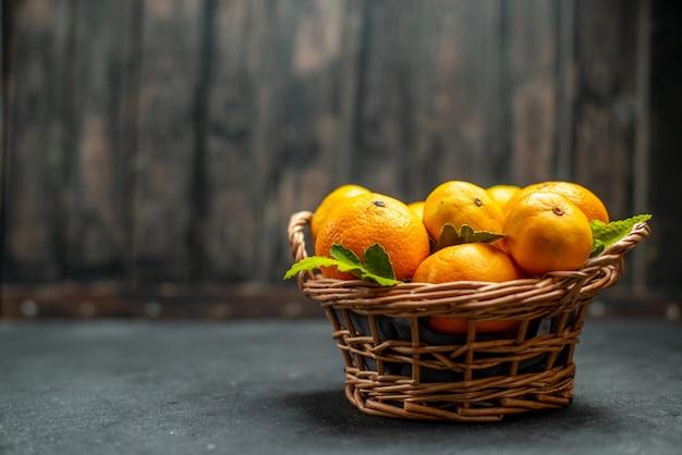 Vista frontal de tangerinas frescas em cesta de vime em local escuro