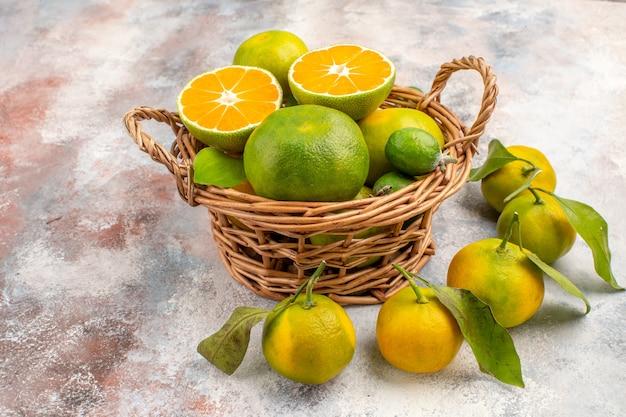 Vista frontal de tangerinas frescas em uma cesta de vime cercadas por tangerinas em um fundo nu