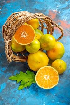 Vista frontal de tangerinas frescas na cesta de vime na superfície azul