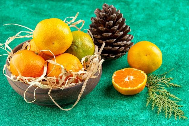 Vista frontal de tangerinas frescas suculentas dentro do prato em cor de fundo verde foto de frutas cítricas ácidas exóticas