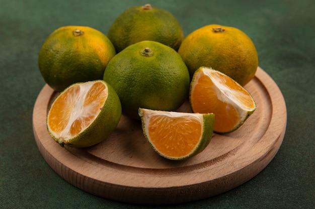 Vista frontal de tangerinas verdes em um suporte em uma parede verde