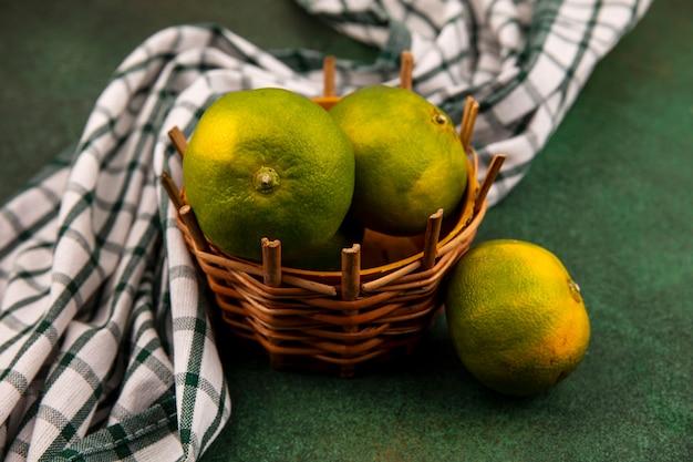Vista frontal de tangerinas verdes em uma cesta com uma toalha xadrez em uma parede verde
