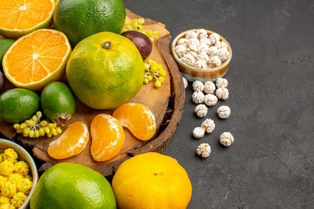 Vista frontal de tangerinas verdes frescas com feijoas e doces no espaço escuro