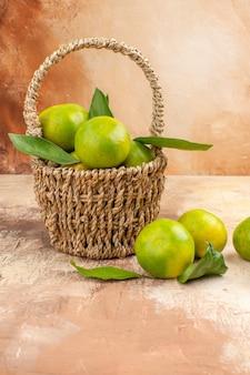 Vista frontal de tangerinas verdes frescas dentro da cesta com fundo claro suco foto cor fruta suave