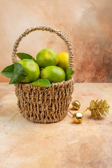 Vista frontal de tangerinas verdes frescas dentro de uma cesta com fundo claro de frutas suaves foto suco natal