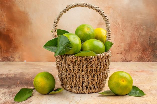 Vista frontal de tangerinas verdes frescas dentro de uma cesta no fundo claro de frutas suaves foto cor de natal