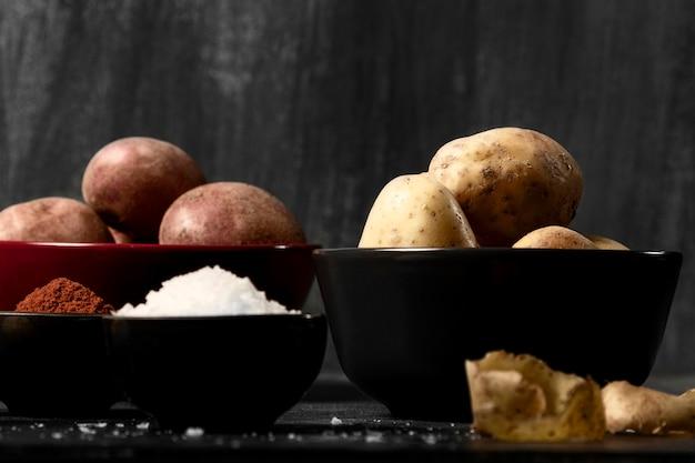 Vista frontal de tigelas com batatas e especiarias