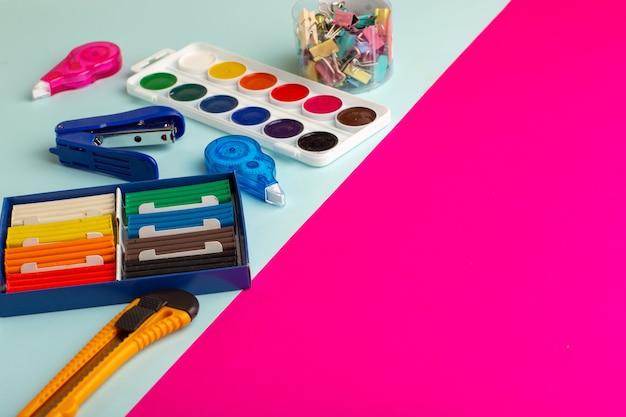 Vista frontal de tintas coloridas com plasticinas na superfície azul-rosa