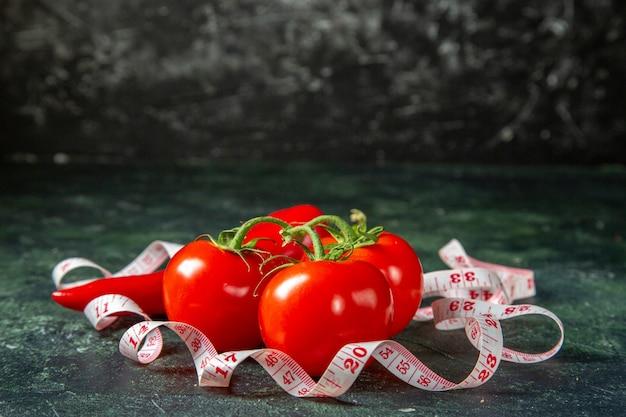 Vista frontal de tomate fresco, pimentão vermelho e medidor em superfície de cores escuras com espaço livre