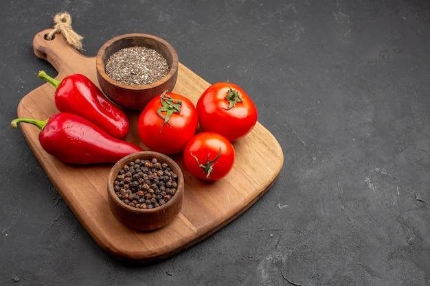 Vista frontal de tomates frescos com temperos e pimenta vermelha no espaço escuro