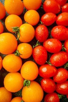 Vista frontal de tomates laranja com tomates em uma superfície verde escura