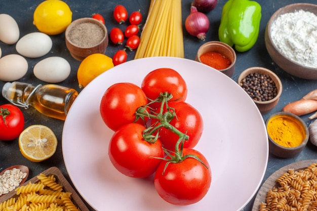 Vista frontal de tomates vermelhos com temperos de vegetais e massas crus no escuro