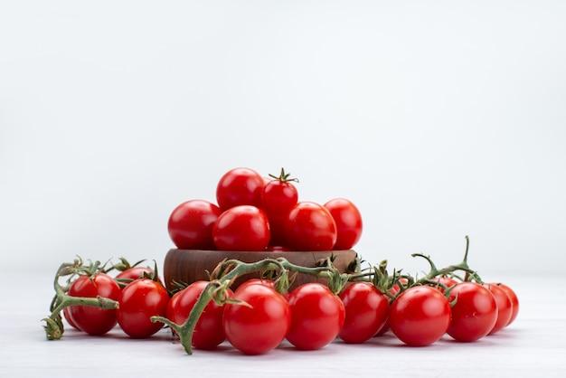 Vista frontal de tomates vermelhos frescos alinhados em alimentos vegetais brancos, comida crua, comida