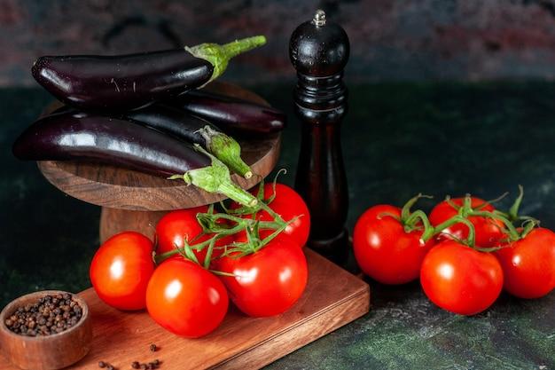 Vista frontal de tomates vermelhos frescos com berinjelas em fundo escuro