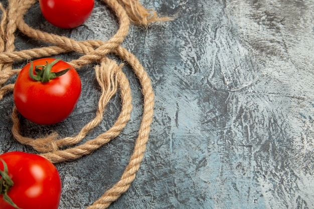 Vista frontal de tomates vermelhos frescos com cordas