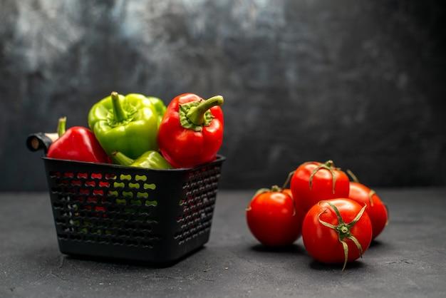 Vista frontal de tomates vermelhos frescos com pimentão no fundo escuro salada de foto colorida de refeição madura
