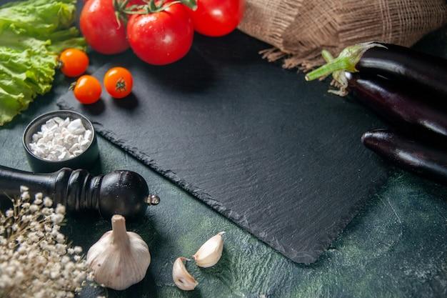 Vista frontal de tomates vermelhos frescos em fundo escuro
